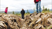 Kaminak Gold VP of exploration Tim Smith (far right) and colleagues explore a trench at the Coffee gold project in the Yukon. Photo by Ian Bickis