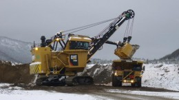 A shovel dumps a load into a haul truck as Thompson Creek strips overburden in preparation to start mining the North pit at Mt Milligan. Credit: Thompson Creek Metals