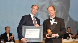 Doug Donnelly (right), Canadian Mining Hall of Fame director and publisher of The Northern Miner, presenting to Gavin McOuat, son of inductee Jack McOuat. Credit:  Canadian Mining Hall of Fame