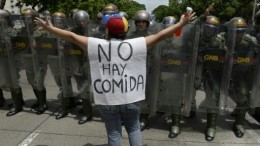 """AFP photo of protester in Caracas, Venezuela, with sign reading """"There is no food."""" Credit: AFP/file."""