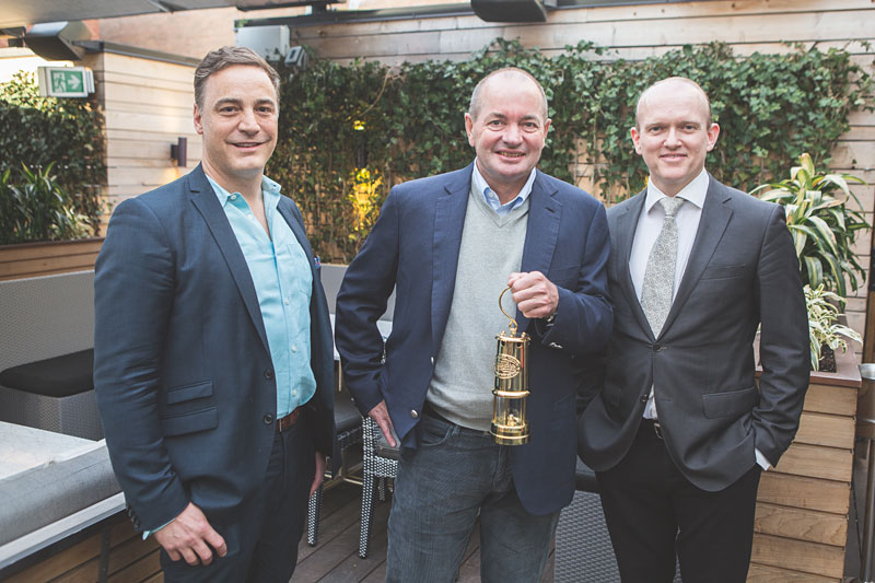 """Presenting Lukas Lundin (centre), principal of The Lundin Group of Companies, with The Northern Miner's """"Mining Person of the Year"""" award for 2015, at the Kasa Moto restaurant in Toronto in May: Anthony Vaccaro (left), publisher of The Northern Miner, and John Cumming, editor-in-chief of The Northern Miner.  Photo by georgematthew.com."""