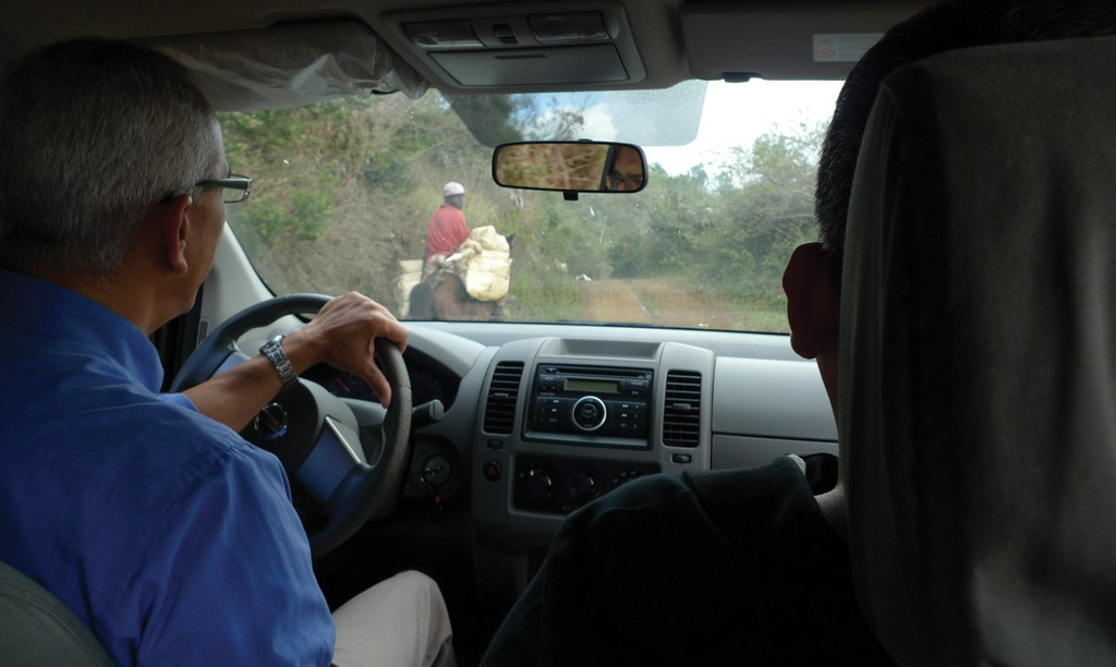 GoldQuest Mining president and CEO Julio Espaillat navigates past a farmer on the road to the Romero copper-gold project in the Dominican Republic.  Photo by David Perri.