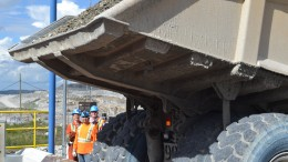 Workers look on as a truck prepares to dump the first load of ore into the primary crusher at Stornoway Diamond's Renard diamond mine in Quebec. Credit: Stornoway Diamond.