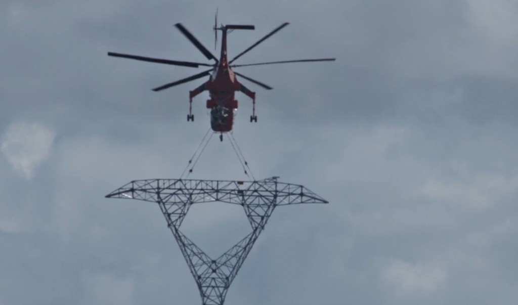 "Screenshot from ""Koneline: our land beautiful"" showing a helicopter transporting a tower for the Northwest Transmission Line in northwestern B.C."