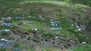 At Minera IRL's Ollachea gold property in Peru, showing areas mined by local artisanal miners at the bottom. The house near the top with the blue drums is where a second mine portal will be and the flat area is where a tails paste plant will be located. Photo by Paul Harris.