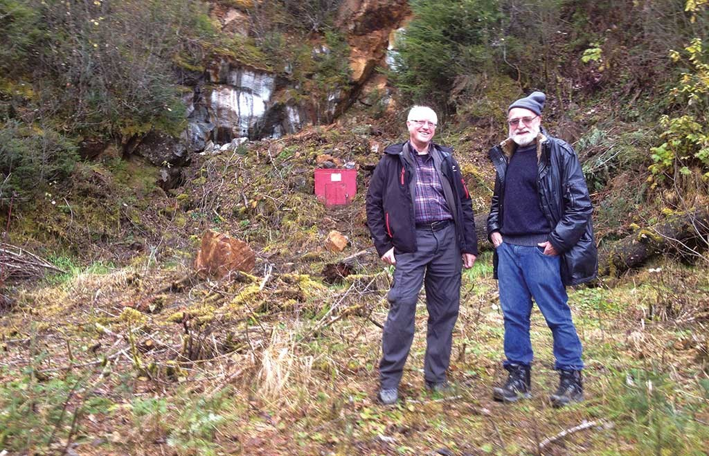 Skeena Resources' chief geologist Ron Nichols (left) and chairman Ron Netolitzky standing in front of a reclaimed adit at the Snip gold project in British Columbia. Photo by Lesley Stokes.