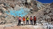 A group poses in front of visual copper at Coro Mining's Berta project in Chile. Credit: Coro Mining.