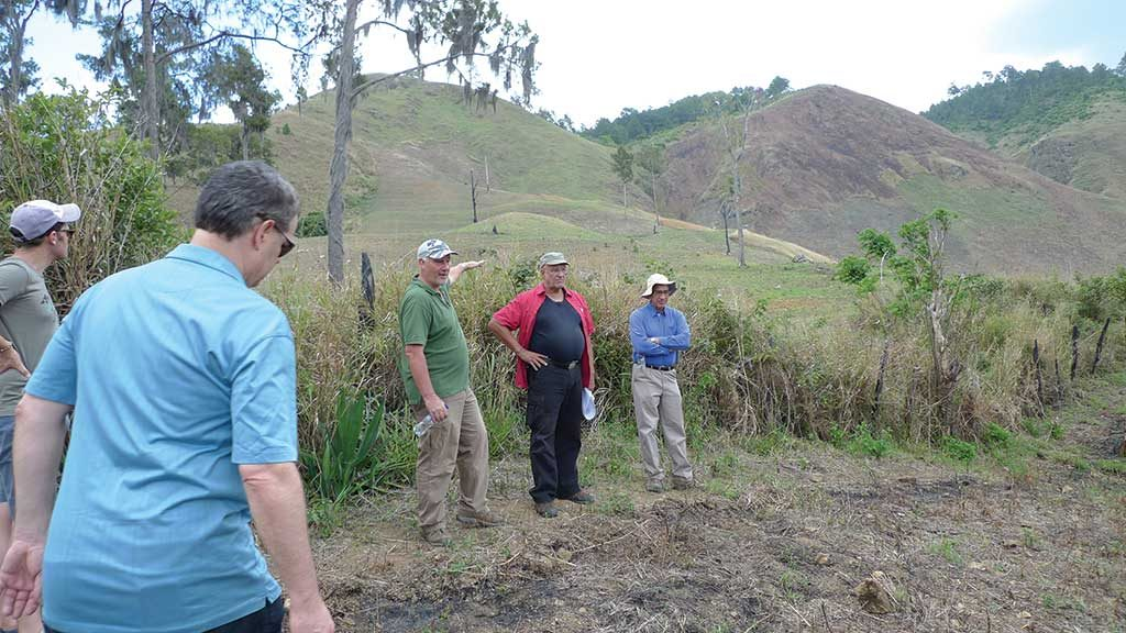 GoldQuest Mining executive chairman Bill Fisher (left) points to a possible mill site at the Romero project in the Dominican Republic, as engineering manager Jean-Pierre Leblanc (middle) and president and CEO Julio Espaillat look on. Photo by David Perri.