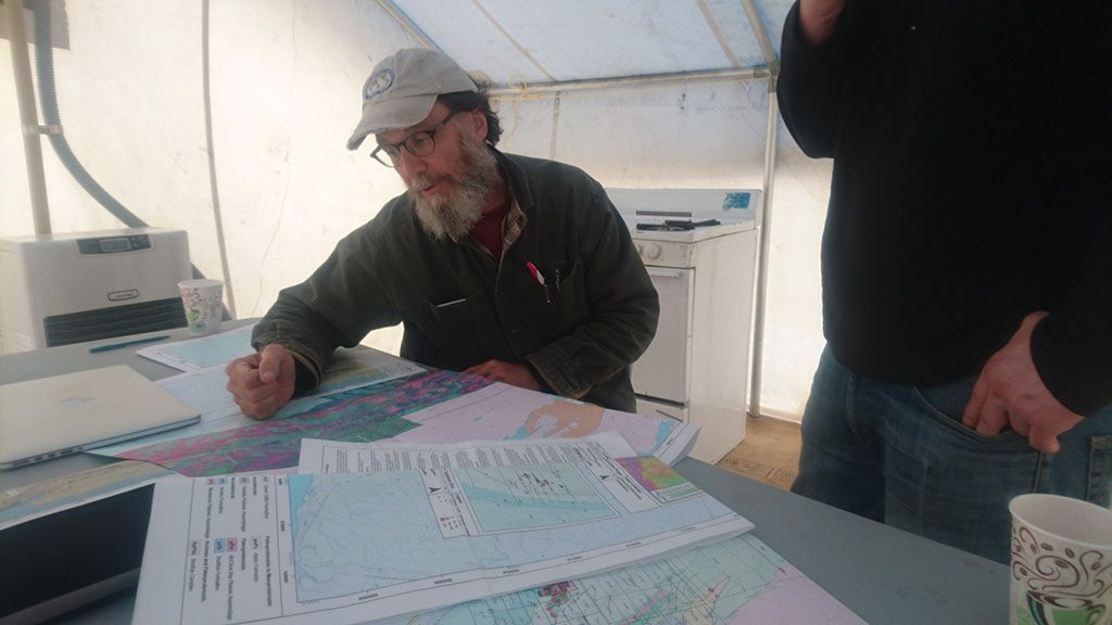 Aston Bay Holdings' chief geologist David Broughton looks over maps of the Storm copper project in Nunavut. Credit: Aston Bay Holdings.