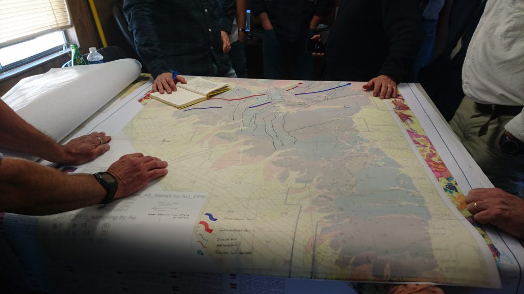 Northern Empire staff analysts huddle around property maps on the Sterling gold property. Photo by Richard Quarisa.
