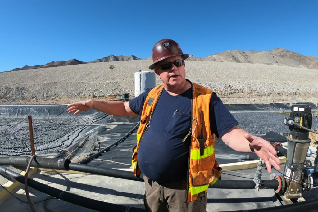 Mine manager Chuck Steven giving a tour of the property. The tailings pond behind him is full of balls that keep out birds. Photo by Richard Quarisa.