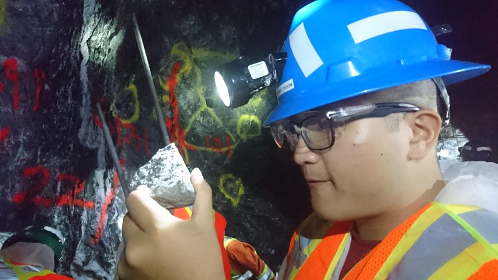 Jeremy Poon, associate with Raymond James, examines a piece of ore underground at Island Gold. Photo by Richard Quarisa.