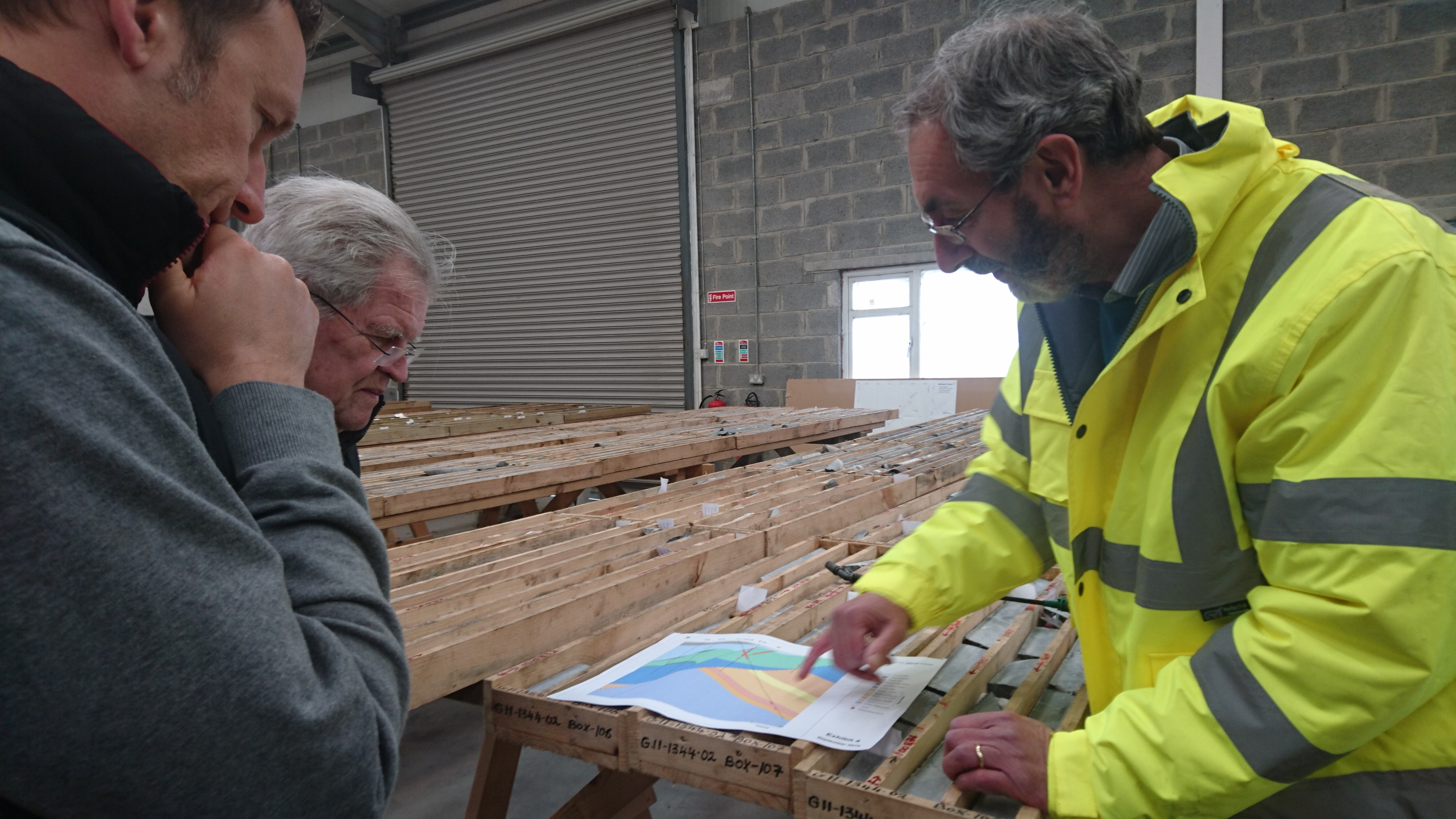 Staff (right) at Group Eleven's core shack discusses Ballinalack's geology with company CEO Bart Jaworski (left) and writer Bob Moriarty (center). Photo by Richard Quarisa.