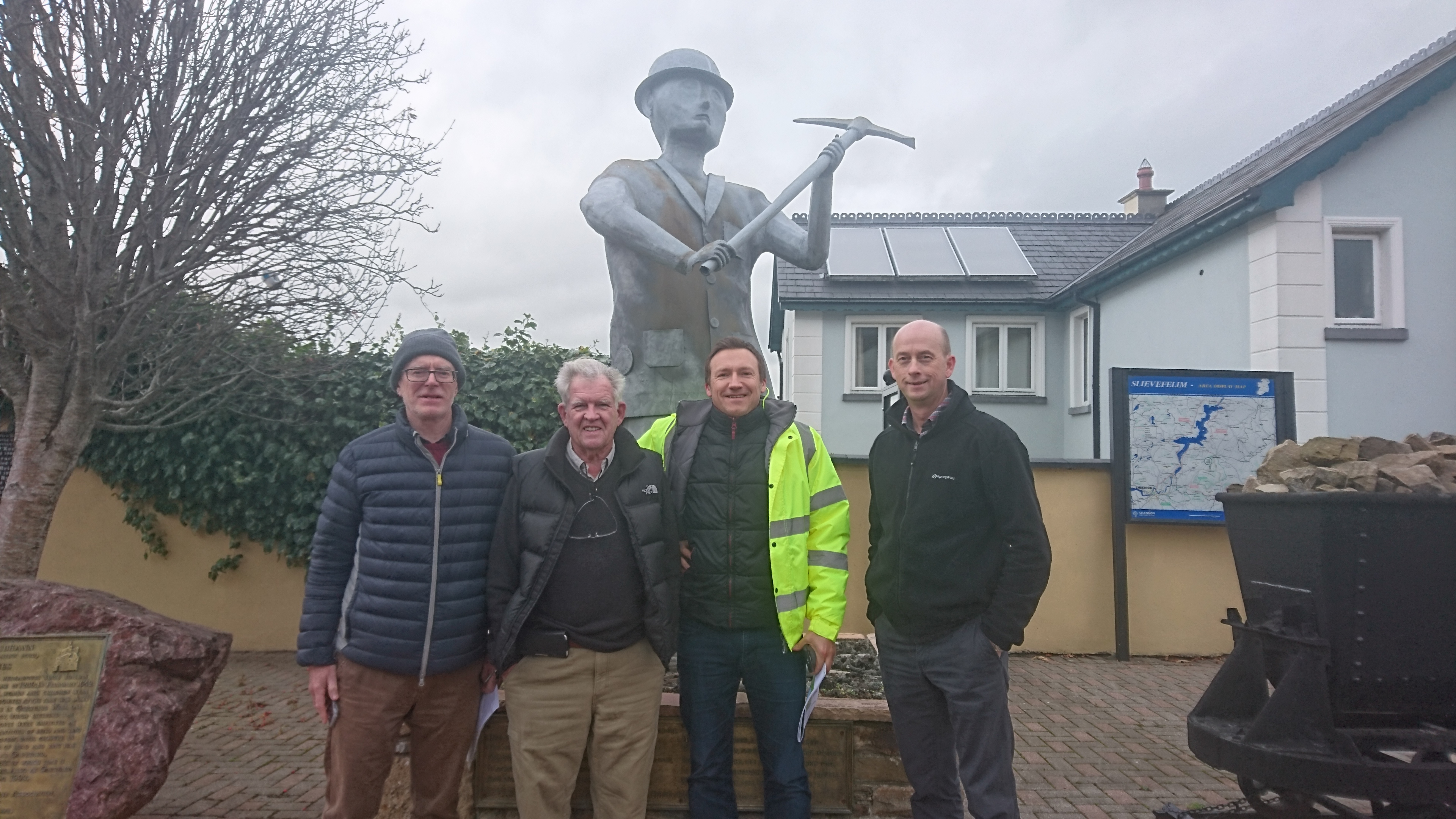 From left to right: Group Eleven vice president of exploration strategy John Barry, writer Bob Moriarty, company CEO Bart Jaworski and company chief operations officer David Furlong pose in front of a statue in the town of Silvermines while on a site visit to Ireland. Photo by Richard Quarisa.