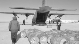 Workers unload fuel and supplies from a Hercules C-130 transport aircraft at the Igloolik Airport.