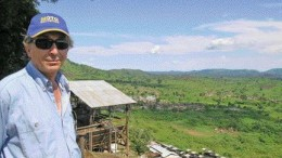 Moto Goldmines project manager Greg Smith stands above a valley surrounding the company's prospective gold property in northeastern Congo. Behind him is a Belgian-built mill near the Durba gold mine, which still operates when there is sufficient feed.