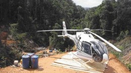 By Stephen StakiwA helicopter on Petaquilla Minerals' Molejon gold project. A drill rig downslope is visible in the background.