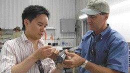BY SUSAN KIRWINAaron Chan of Canaccord Capital gets a lesson from Alexandria Minerals president Eric Owens on how to use a hand lens to examine drill core.