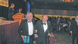 """Canadian Mining Hall of Fame inductee Prof. Donald """"Digger"""" Gorman (right) is escorted from the podium by Jeff Fawcett, professor emeritus in the department of geology at the University of Toronto."""