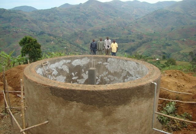 Banro Foundation staff with the tank for a potable water system near the Twangiza gold mine project in the eastern DRC. It serves 18,000 people and consists of 19,000 metres of piping.