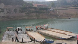 Barges are loaded with ore for transport across the reservoir. Source: Silvercorp Metals