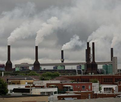 The smoke stacks at Rio Tinto's aluminum smelter rise above the rooftops in Shawinigan, Quebec. Photo by Michel Talbot.
