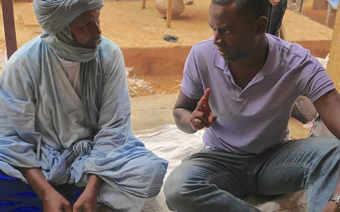 Great Quest Metals CEO Jed Richardson (right) speaks with a merchant in Gao, Mali. Credit: Great Quest Metals