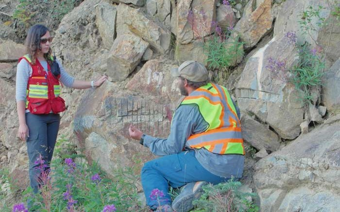 Victoria Gold project geologist Helena Kuikka and Yukon Geological Survey geologist Patrick Sack discuss an outcrop at the Olive zone, part of Victoria's Dublin Gulch gold project in Yukon. Photo by Gwen Preston.