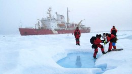 National Research Council personnel drill to measure the properties of multi-year sea ice near Banks Island in the Northwest Territories, with the Canadian Coast Guard's Amundsen icebreaker in the background. Credit: National Research Council