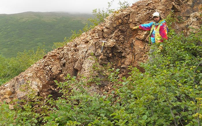 A field worker stands by the outcropping Shumagin vein at Redstar Gold's Unga gold project in Alaska. Credit: Redstar Gold