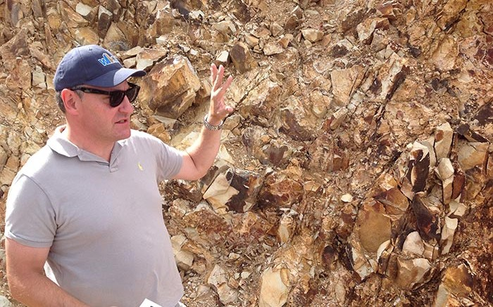 At an outcrop along the drill road, West Kirkland Mining president and CEO Michael Jones explains the geology seen at the Hasbrouck gold project. Credit: Photo by Matthew Keevil.