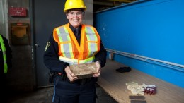 An Ontario Provincial Police officer poses with a freshly poured gold bar at the Mishi gold mine opening in Ontario in 2012. Credit: Wesdome Gold Mines