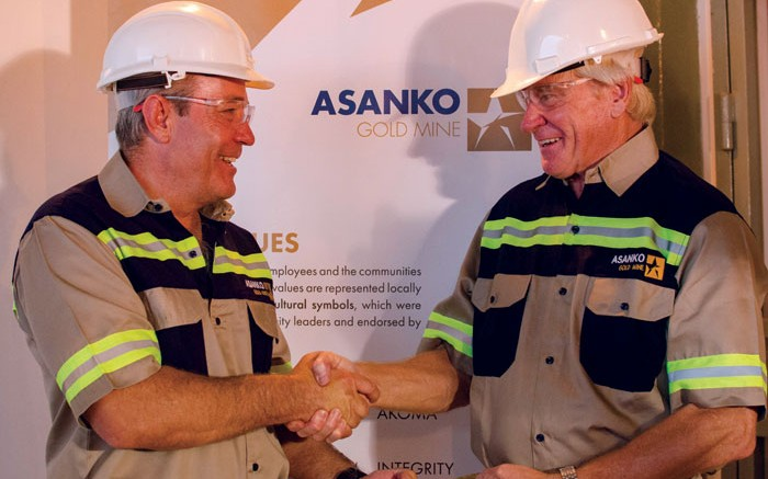 Peter Breese (left), Asanko Gold's president and CEO, and Colin Steyn, chairman, shake hands over a gold bar from the Asanko gold mine in Ghana. Credit: Asanko Gold