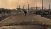A Royal Canadian Mounted Police walking along a fire devastated street in Fort McMurray, Alberta. Credit: RCMP Alberta