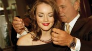 Birks' senior VP John Orrico helps actress Allie MacDonald with a 75-carat rough diamond necklace made with gems from De Beers' Victor mine, in Ontario. Credit: Birks & Mayors.