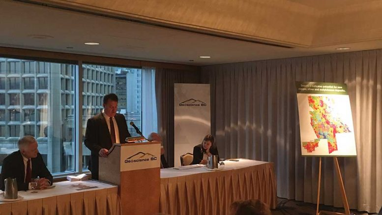 At the Geoscience BC presentation at the Association for Mineral Exploration's Roundup convention in Vancouver, from left: Robin Archdekin, president and CEO of Geoscience BC; Bruce Madu, vice-president of minerals and mining at Geoscience BC; Bill Bennett, B.C.'s minister of energy and mines (behind podium); and Kendra Johnston, AME director. Photo by Lesley Stokes.