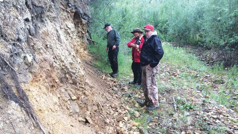 Triumph Gold's vice-president of exploration Tony Barresi (centre) takes notes at an exposure of strongly altered rock on the margin of Triumph's Revenue diatreme in Whirlwind Creek in the Yukon, with placer miner John Gow (left) and Kyle Cashin of the Little Salmon Carmacks First Nation. Credit: Triumph Gold.