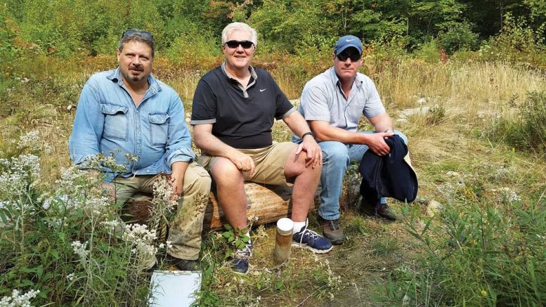 At the Pine Zone discovery hole on New Age Metal's River Valley PGM property in northern Ontario, from left: Richard Zemoroz, project geologist; Harry Barr, founder, chairman and CEO; and Trevor Richardson, president and COO. Photo by Trish Saywell.