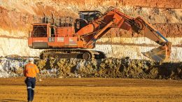 A worker walks towards an excavator and Glencore's Murrin Murrin nickel-cobalt mine in Western Australia. Credit: Glencore.