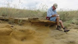 USGS geologist Bradley Van Gosen taking notes while sitting on top of a uranium-bearing calcrete outcrop in the southern United States. Credit: USGS.