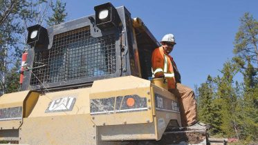 A worker on a tractor at Avalon Advanced Materials' Separation Rapids lithium project in Ontario. Credit: Avalon Advanced Materials.
