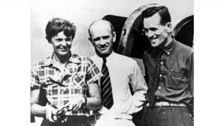 In this photo taken on or about July 2, 1937, American aviator Amelia Earhart (left) and her navigator Fred Noonan (right), pose beside their plane with gold miner F.C. Jacobs at Lae, New Guinea, just before Earhart and Noonan took off in a flight to Howland Island on July 2, during which they disappeared somewhere in the Pacific. Credit: AP.