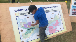 Studying a geological map at the Sandy Lake First Nation Treaty Days Information on Mineral Exploration day in June 2018. Credit: Sandy Lake Gold.