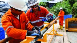 Drillers extracting core on the drill pad. Credit: SolGold.