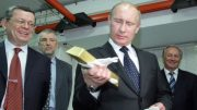 Vladimir Putin, then Russia's prime minister, with a gold bar during a visit in 2011 to the Central Bank of Russia's gold vault. Credit: AFP.