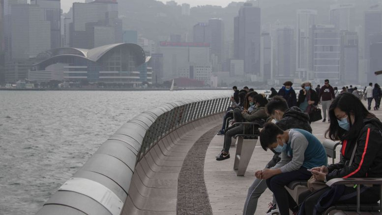 Mask-wearing people in February 2020 sitting at the Tsim Sha Tsui Promenade in Hong Kong amid the Wuhan coronavirus outbreak. Credit: Matt Leung/iStock.