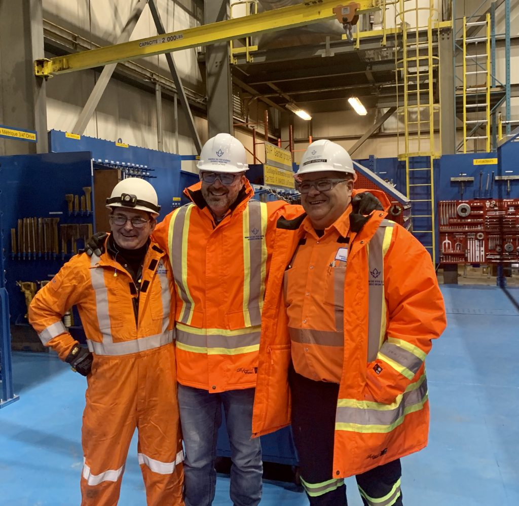 YMP award winner David Cataford (centre) in the mine garage at the Bloom Lake iron ore mine.
